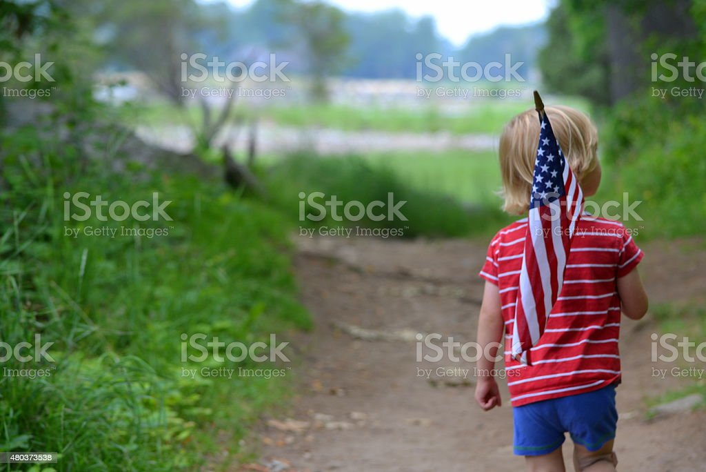 Young boy carrying American Flag stock photo
