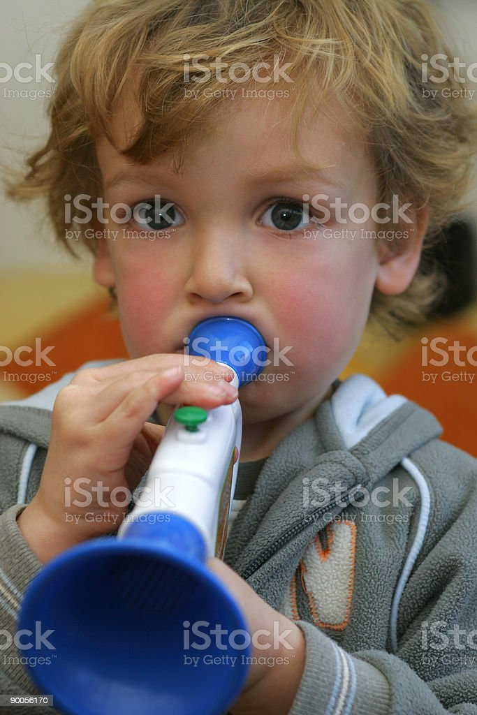 Young Boy Child Blowing A Toy Trumpet royalty-free stock photo