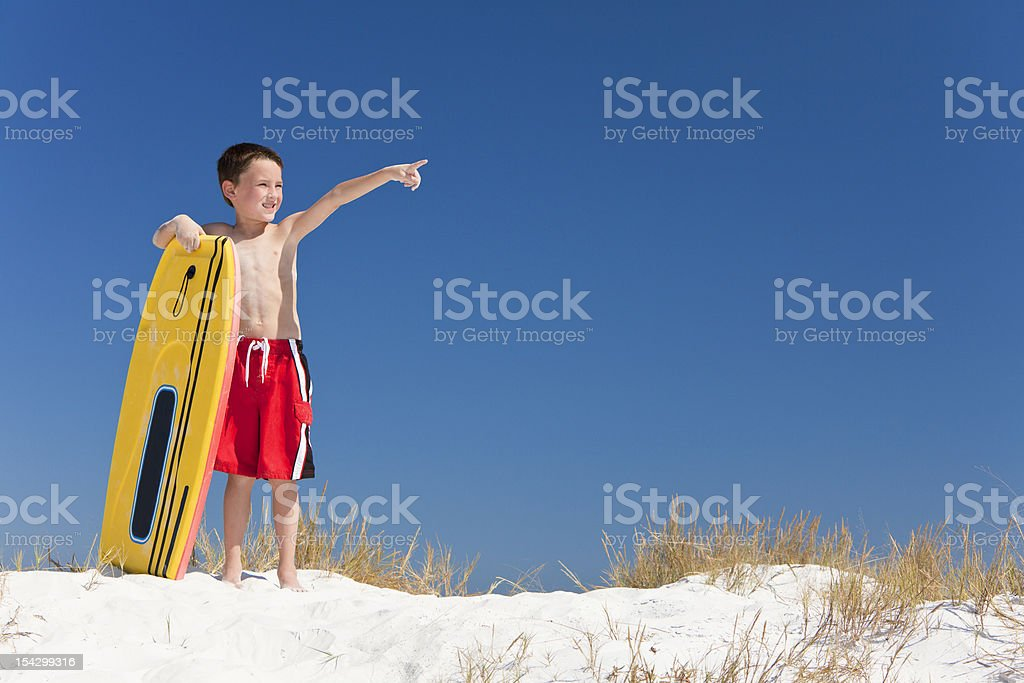 Young Boy Child on A Beach with Surfboard Pointing stock photo