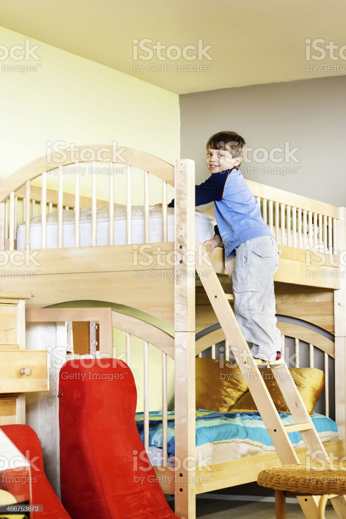 Young boy climbing ladder on wooden bunk bed in child's room royalty-free stock photo
