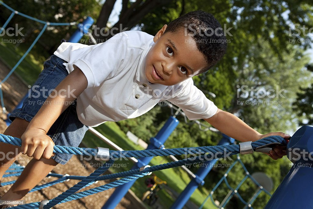 Young boy climbing rope structure royalty-free stock photo