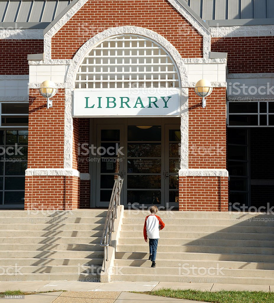 Young boy climbing steps to a library building royalty-free stock photo