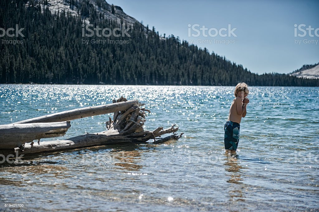 Young boy cold in a high altitude lake stock photo