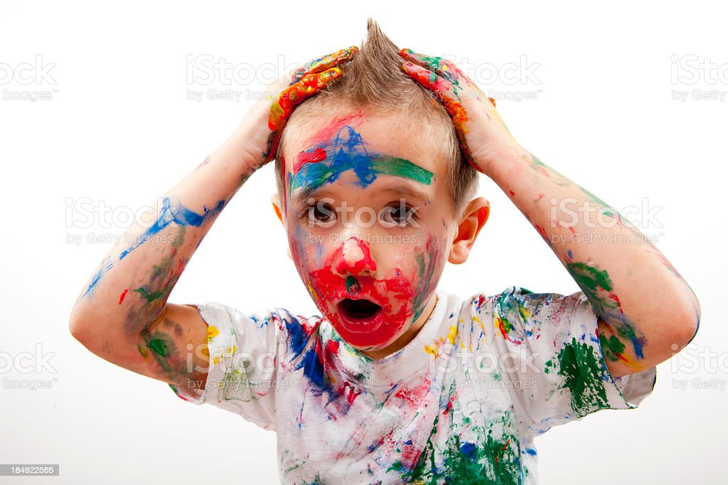 Young boy completely covered in many colors of paint stock photo