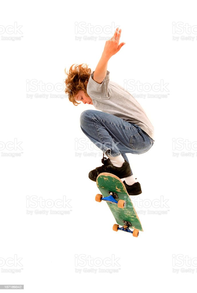 Young boy completing a skateboarding trick royalty-free stock photo