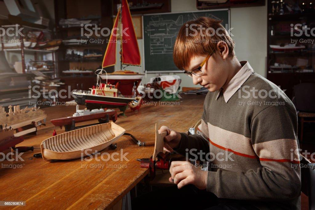 Young boy constructing a ship model stock photo