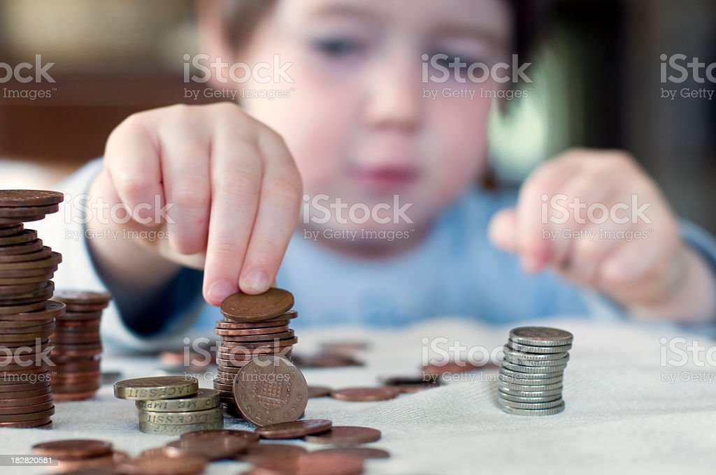 A young boy counting his piggy bank money stock photo