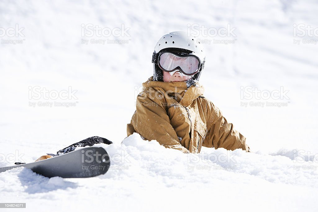 Young boy covered in snow with skis stock photo