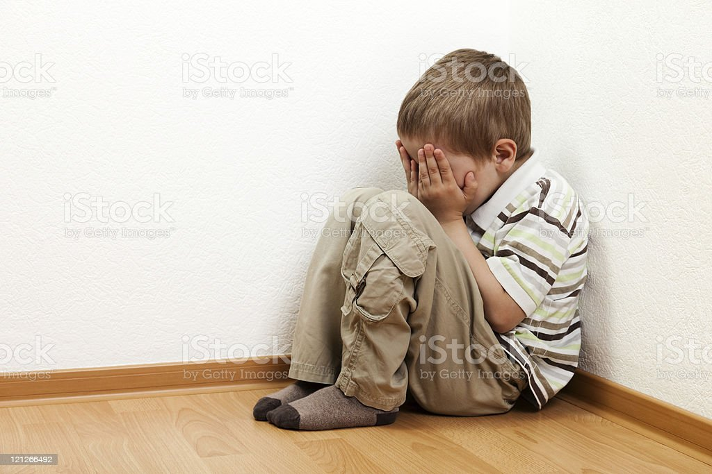 Young boy crying in room corner royalty-free stock photo