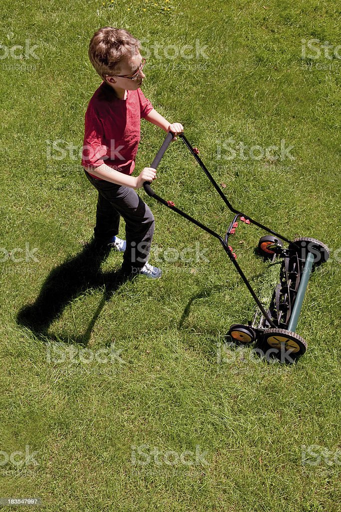 Young boy cutting the lawn with non motorized push mower stock photo