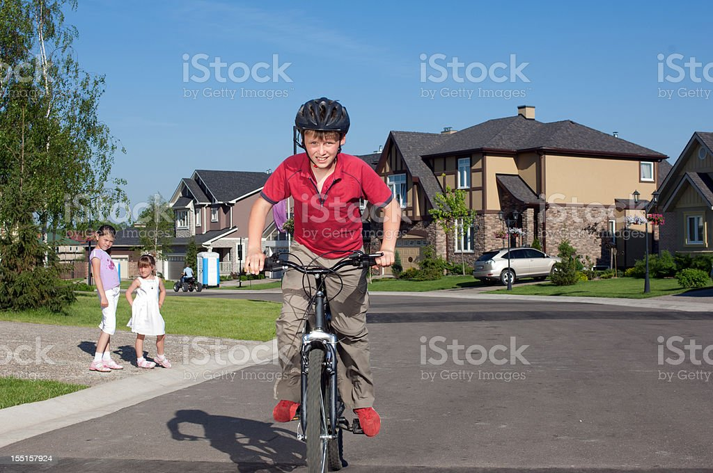 Young boy cycling by suburban street royalty-free stock photo