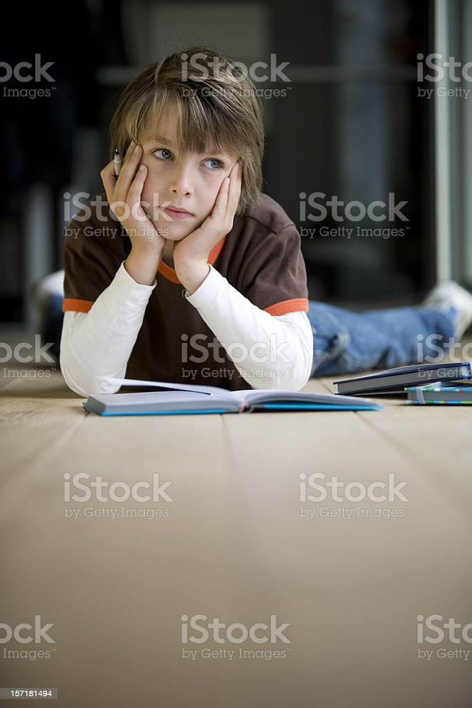 Young boy daydreaming instead of doing his homework royalty-free stock photo