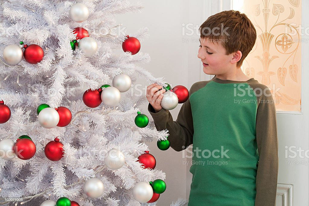 Young boy decorating Christmas tree royalty-free stock photo