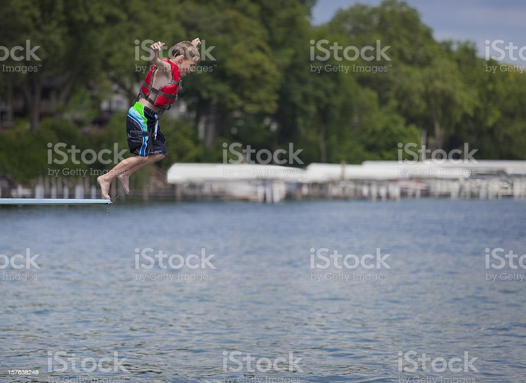 Young boy diving into lake royalty-free stock photo