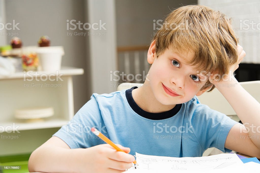Young boy doing homework in the kitchen royalty-free stock photo