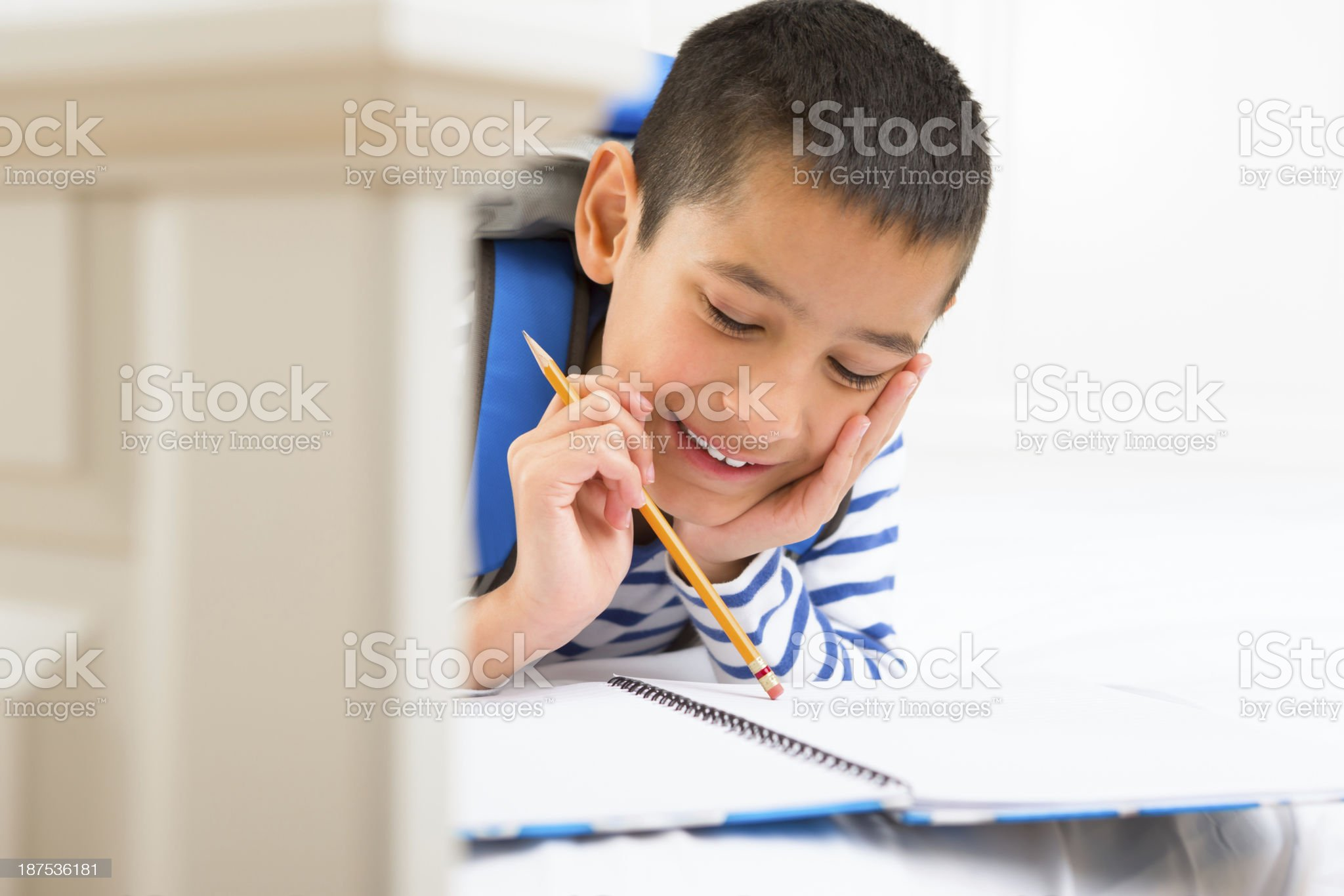 Young boy doing homework on his bed royalty-free stock photo