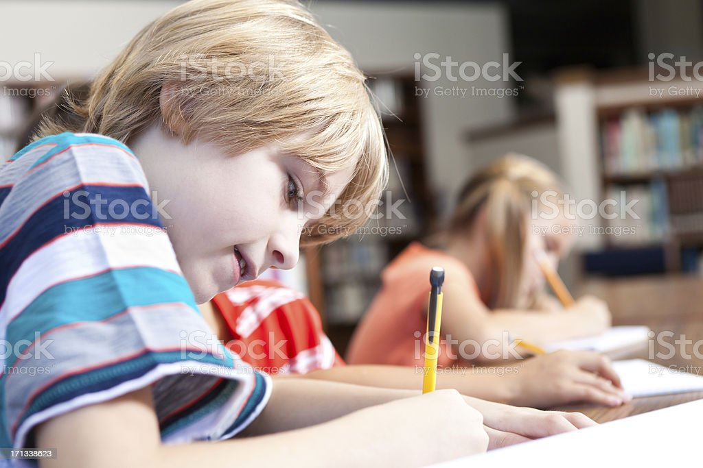 Young boy doing school work in class with fellow students royalty-free stock photo