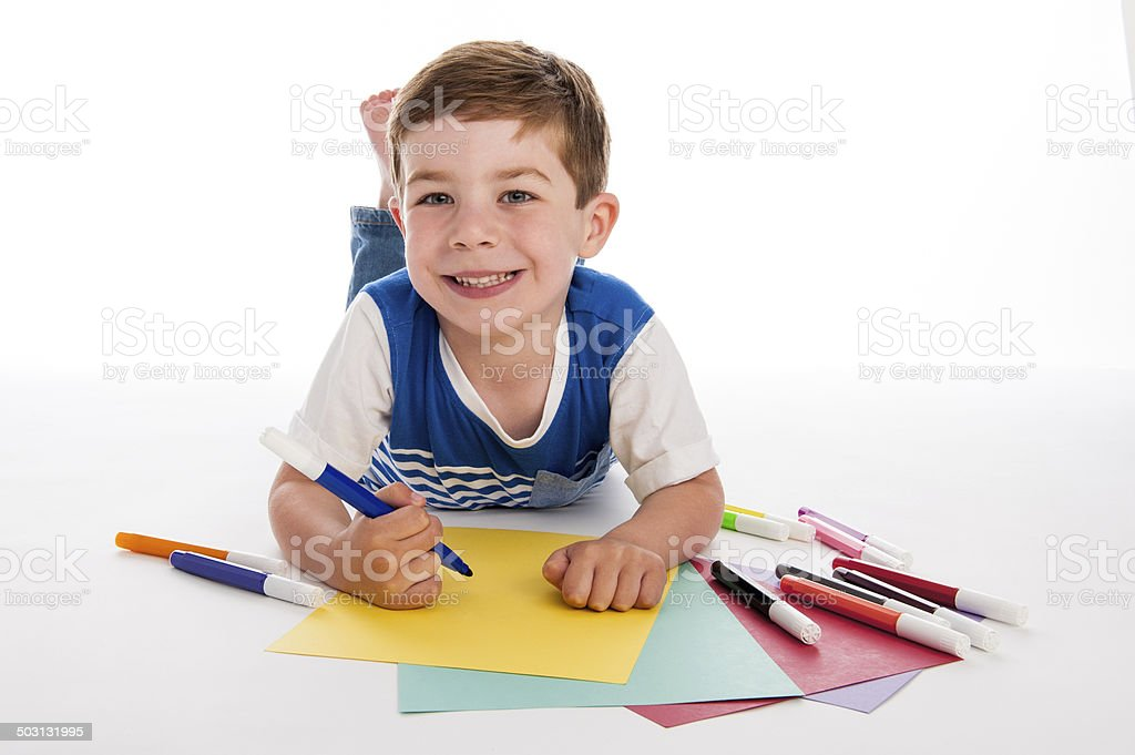 Young Boy Drawing on Colored Paper. stock photo