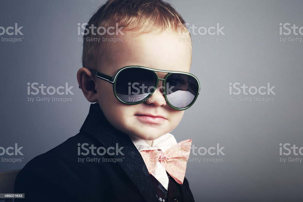 Young boy dressed as a gentleman with sunglasses stock photo