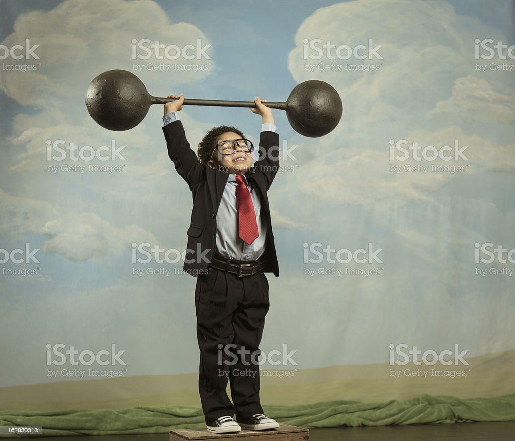 Young Boy Dressed as Businessman Lifting Barbell stock photo