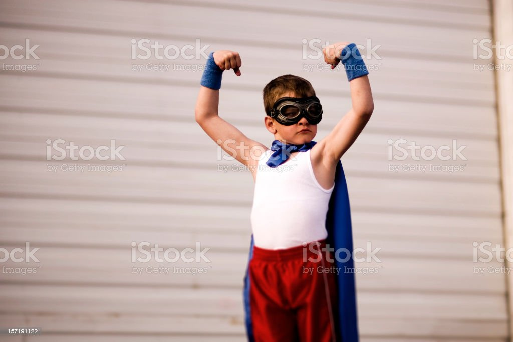 Young Boy Dressed as Supehero Flexes Biceps stock photo
