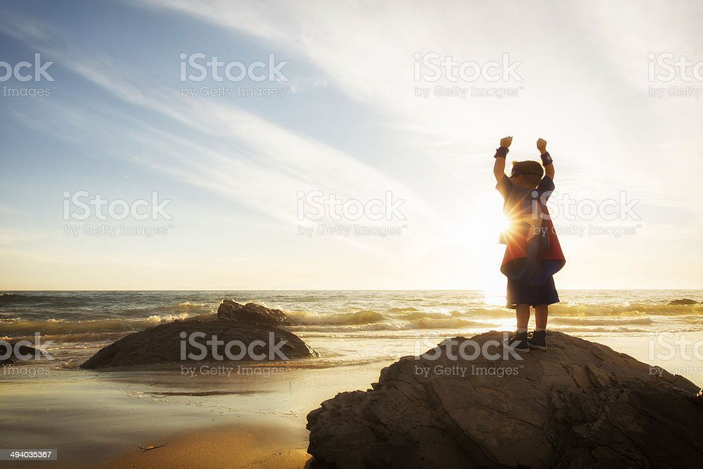 Young Boy Dressed as Superhero at Beach During Sunset stock photo