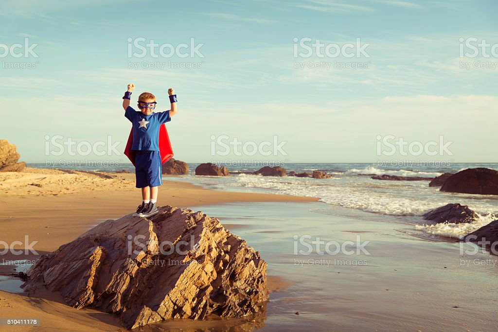 Young Boy Dressed as Superhero flexes Muscles on Beach stock photo