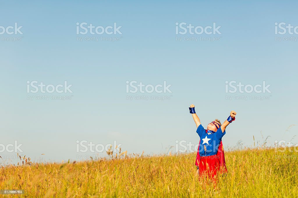 Young Boy Dressed as Superhero Imagines Flying stock photo