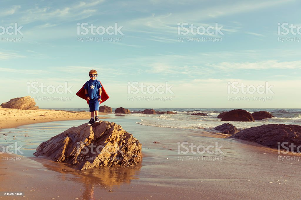 Young Boy dressed as Superhero on California Beach stock photo