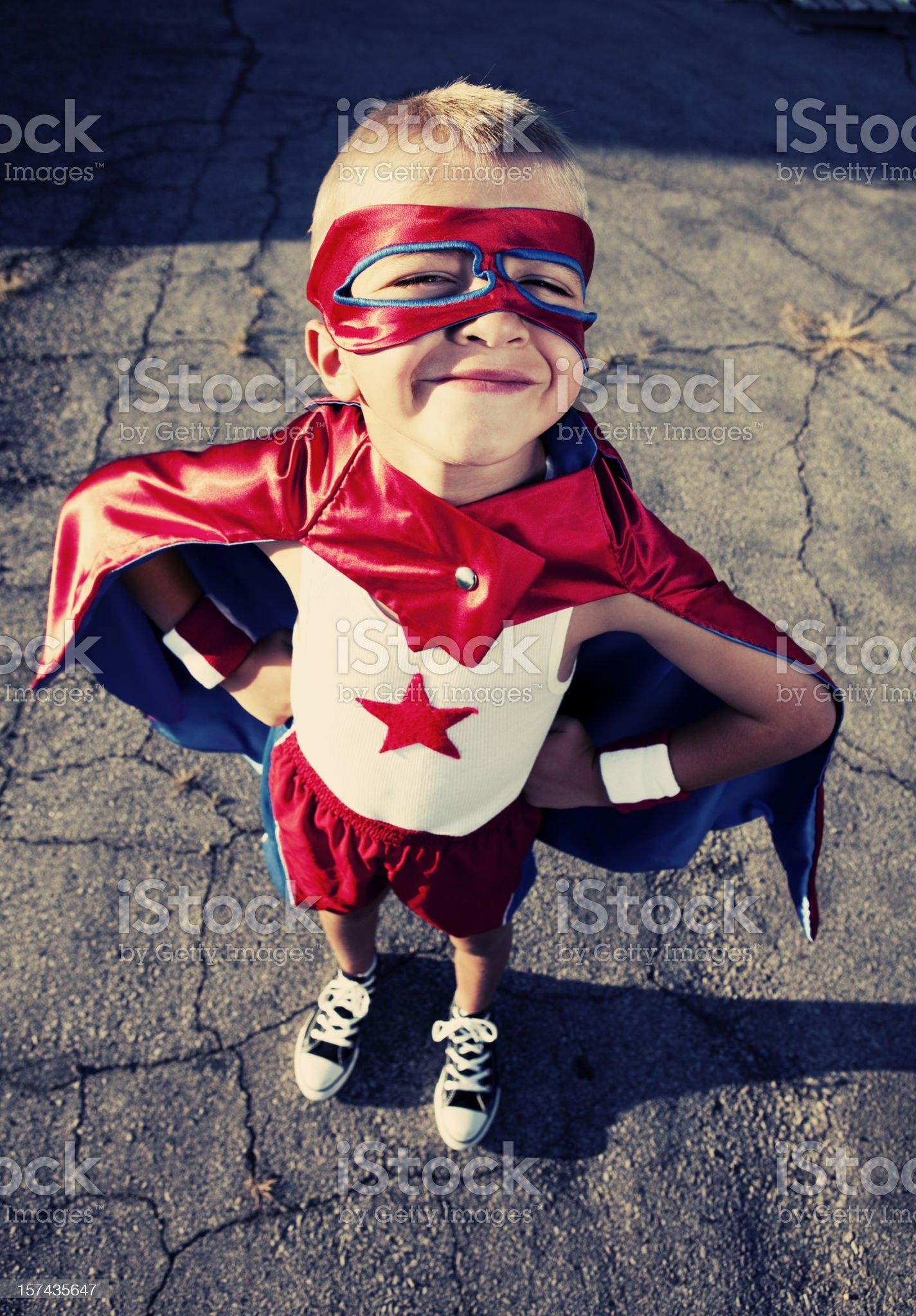 Young Boy Dressed as Superhero Smiles on Blacktop royalty-free stock photo