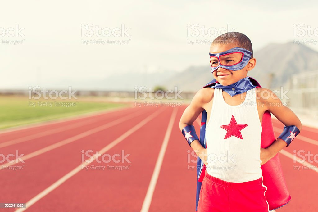 Young Boy Dressed as Superhero Stands on Running Track stock photo