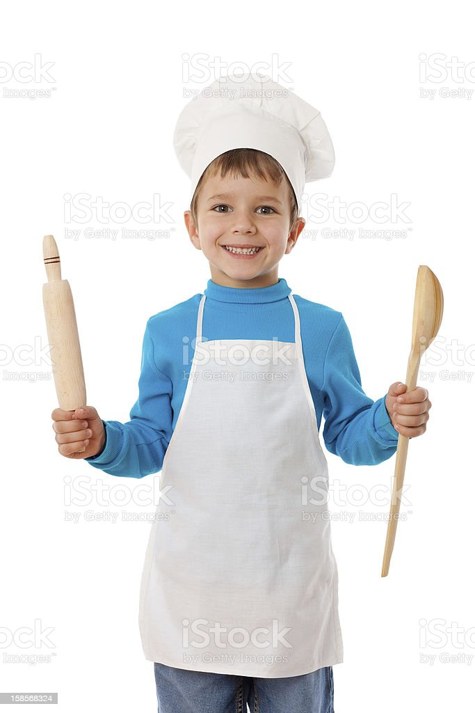 Young boy dressed in a chefs outfit with ladle and spoon stock photo