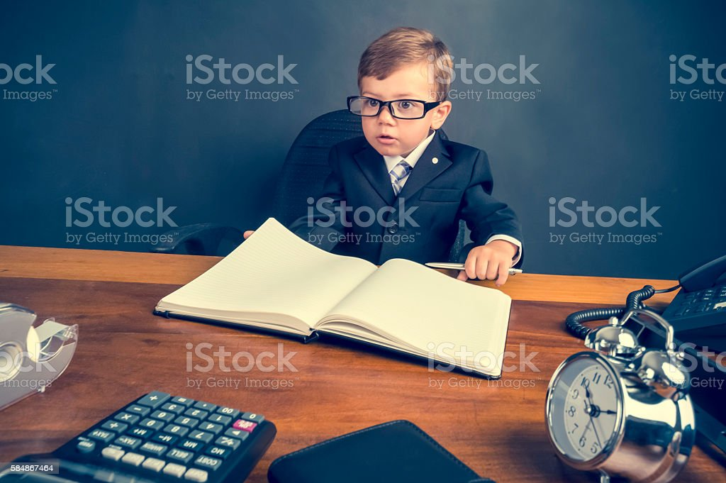 Young boy dressed in a suit working stock photo