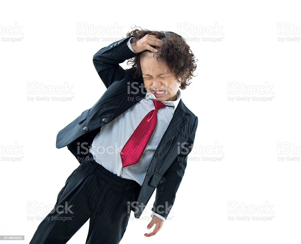 Young boy dressed like businessman scratching his head stock photo