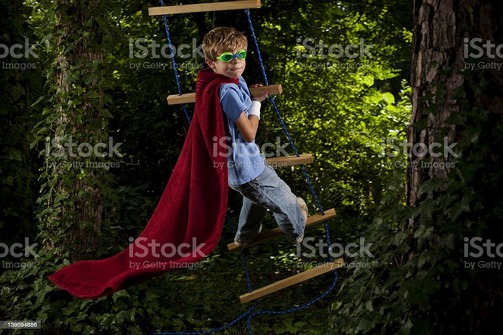 Young boy dresses super hero clothes while climbs a stair royalty-free stock photo