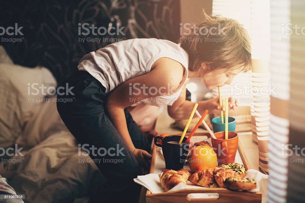 Young boy drinking beverage from mug stock photo