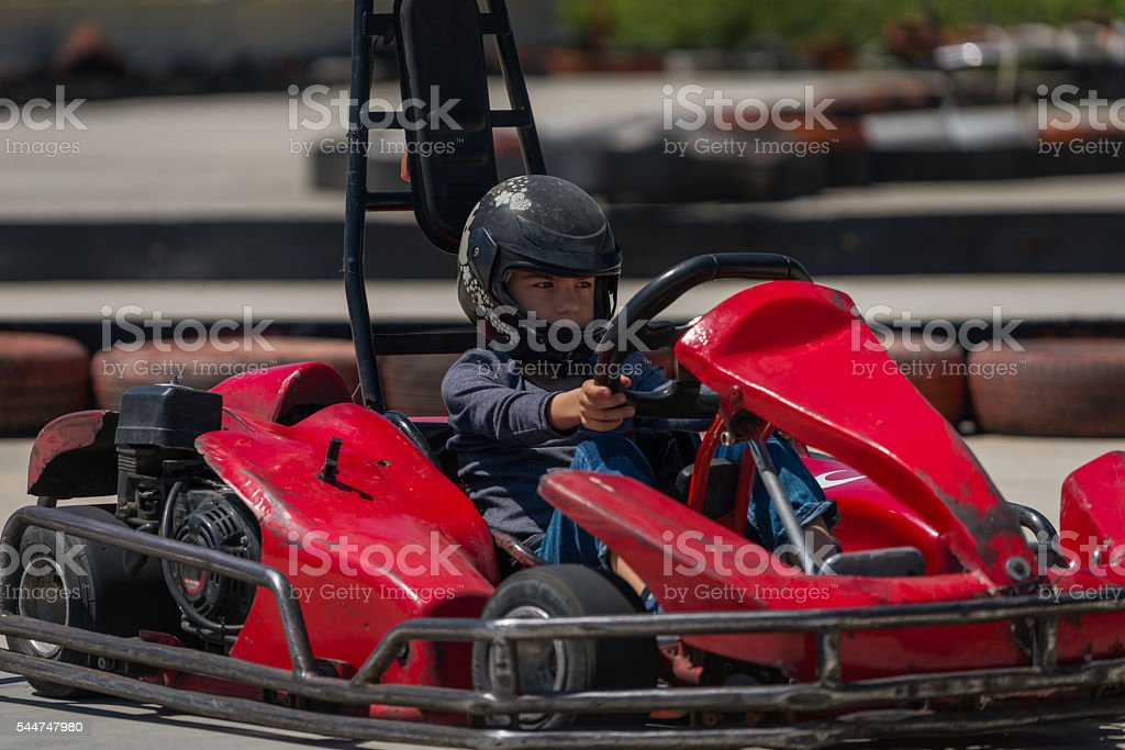 Young boy driving a go-cart on a race track stock photo