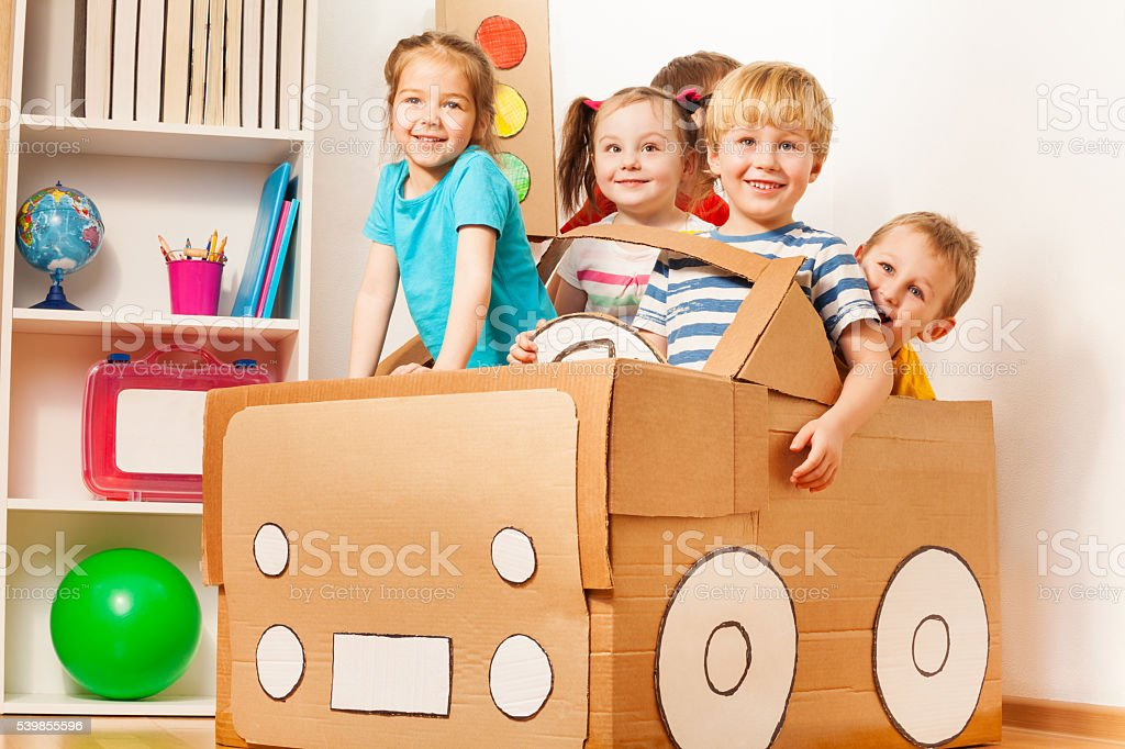 Young boy driving his friends in cardboard car stock photo