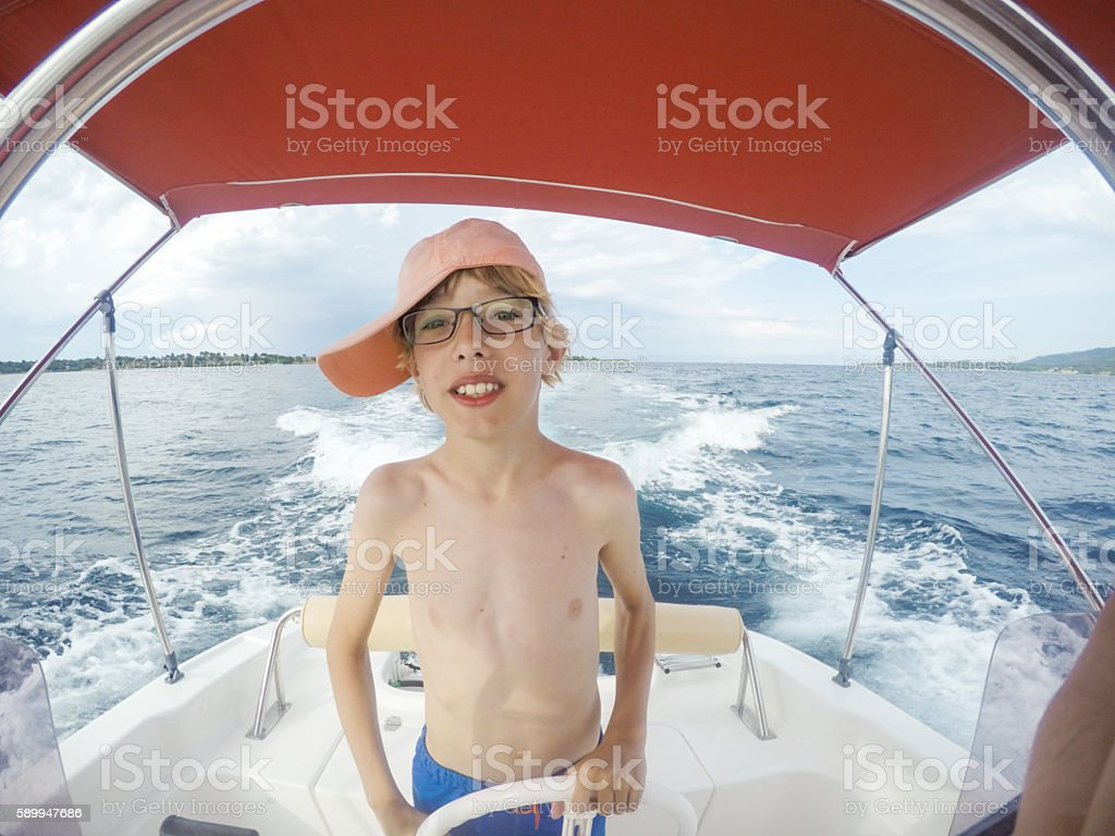 Young boy (10-11 years)  driving speedboat stock photo