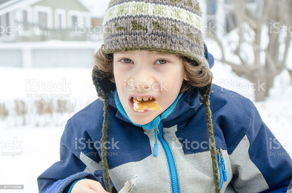 Young boy eating maple syrup taffy outside stock photo