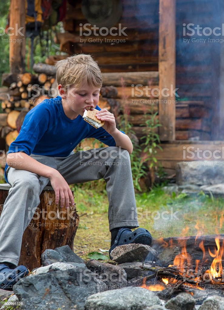 Young boy eating marshmallow smores over campfire stock photo