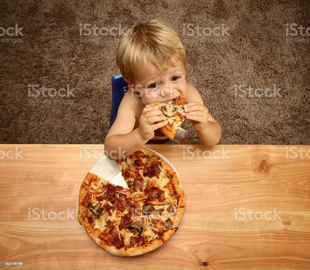 Young boy eating pizza at wooden table royalty-free stock photo