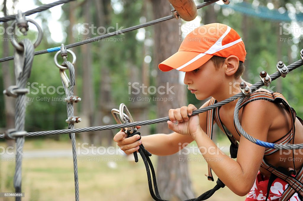 Young boy engaged climbing at the rope course. stock photo