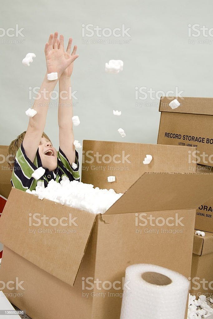 Young boy enjoying the boxes on moving day. Packing, unpacking. royalty-free stock photo