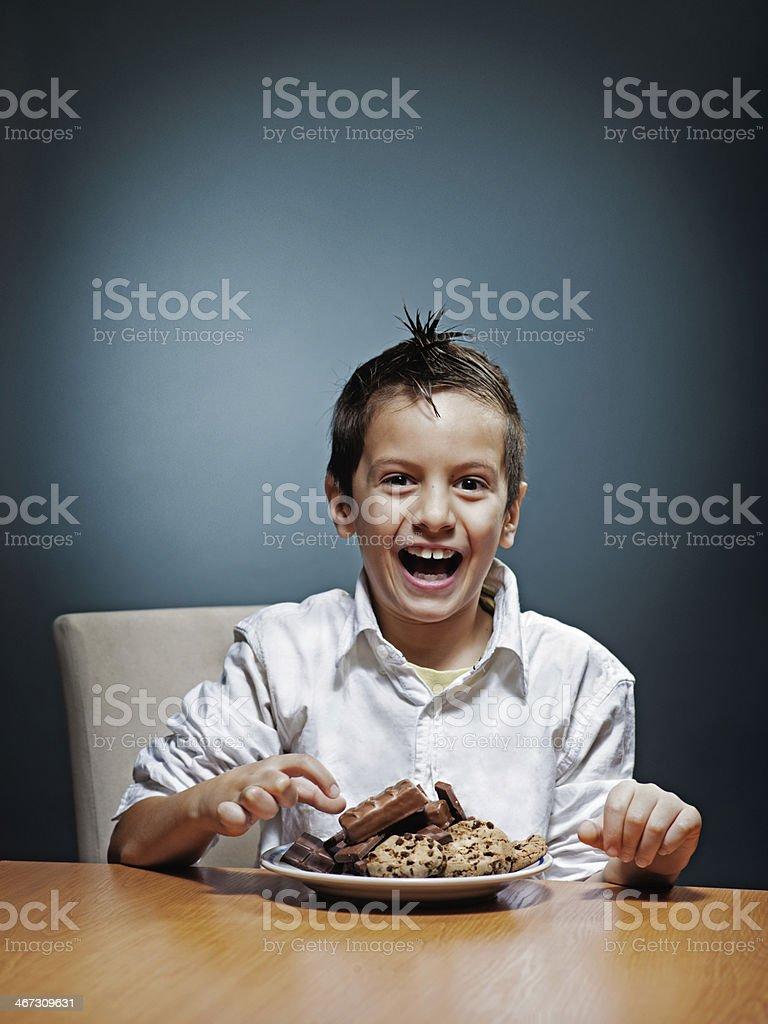 Giovane ragazzo felice di mangiare alcune dolci foto stock royalty-free