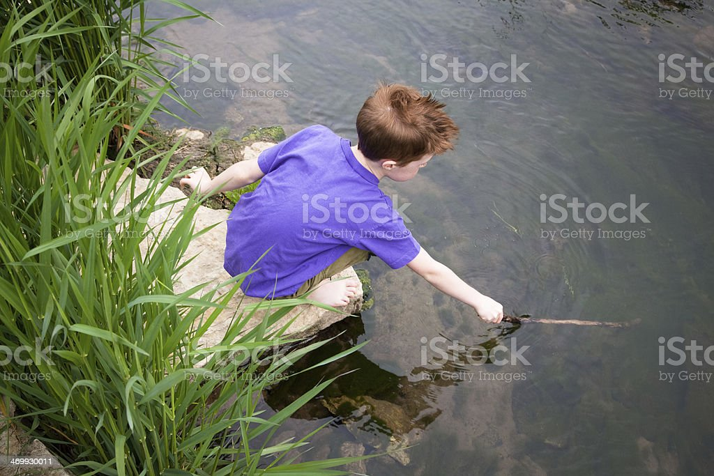 Young boy exploring the underwater nature with a stick stock photo