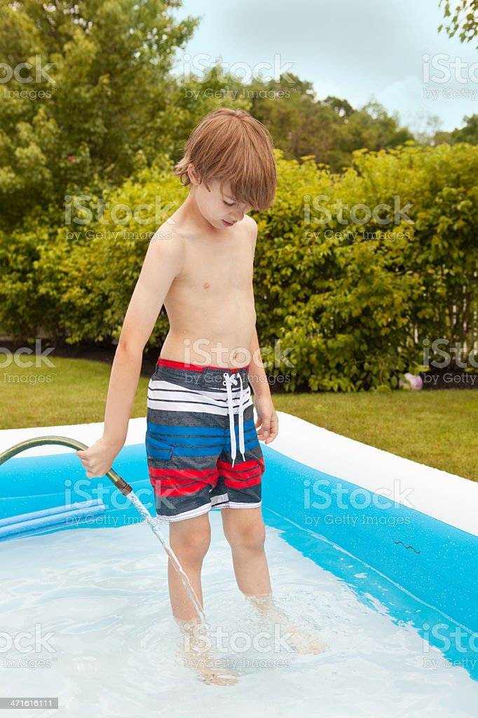 Young Boy Filling Up Swimming Pool With Hose royalty-free stock photo