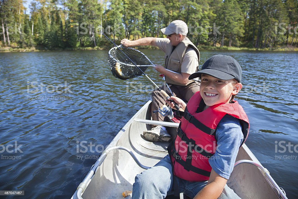 Young boy fisherman smiles at catch of nice walleye stock photo