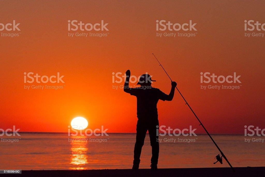 young boy fishing at sunset stock photo