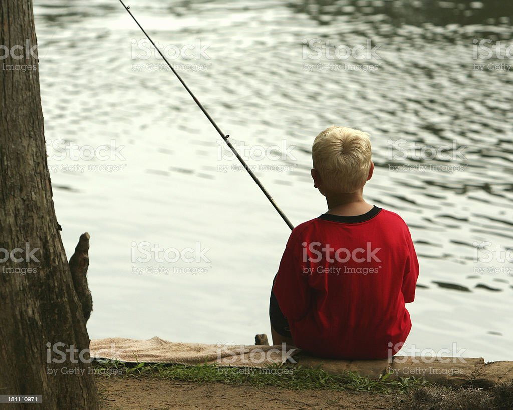 Young Boy Fishing at the Lake's Edge royalty-free stock photo